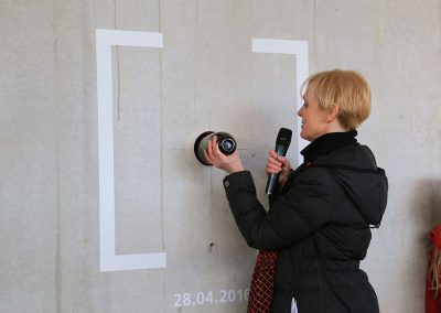 Benita Braun-Feldweg inserts capsule with wishes in wall